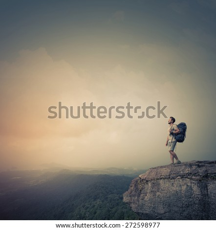 Hiker standing on top of the mountain with backpack