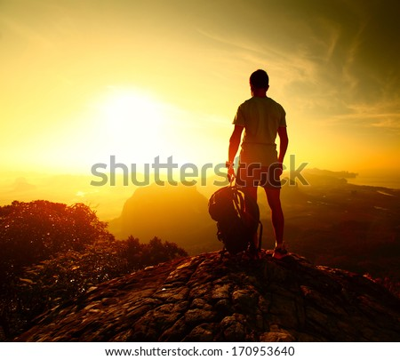 Hiker standing with backpack on top of a mountain and enjoying sunrise - stock photo