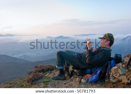 Hiker take a picture in mountains - stock photo