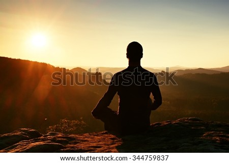 Hiker take a rest and doing Yoga pose on the rocks peak.  Man within misty morning enjoy the scenery