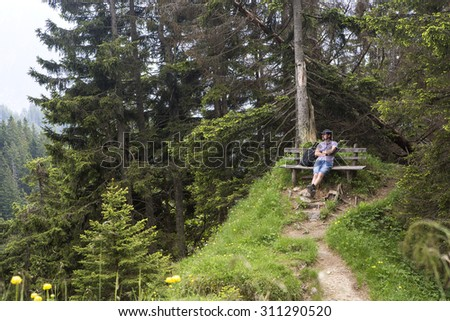 Hiker takes a break and enjoys the view in the Bavarian Alps, Germany - stock photo