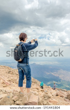 Hiker Taking a Picture with Her Smartphone on a Cloudy Day