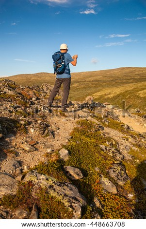 hiker taking photo of mountain landscape with smartphone