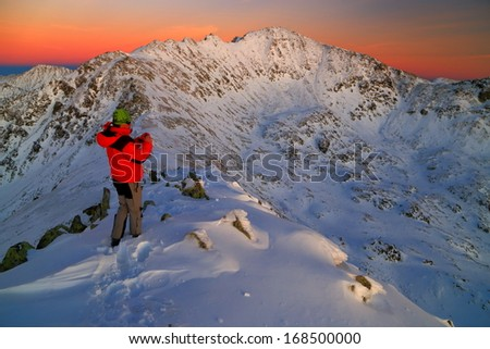 Hiker taking pictures of snowy mountains after sunset - stock photo