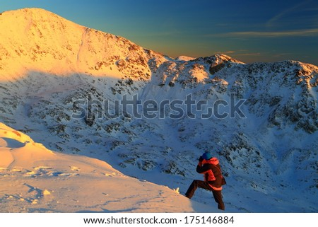 Hiker taking pictures of the landscape at sunset - stock photo