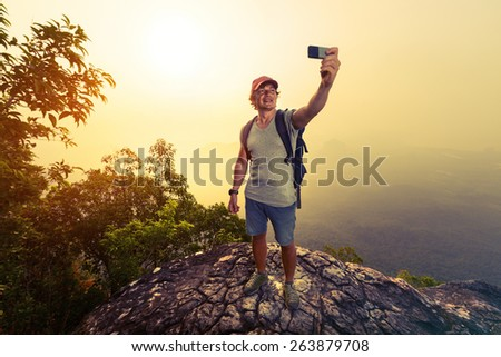 Hiker taking selfie on top of the mountain at sunrise - stock photo