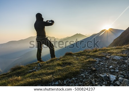 Hiker taking the picture phone the sunrise in the mountains.