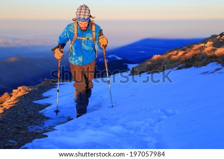 Hiker traverses a snow field on the mountain - stock photo