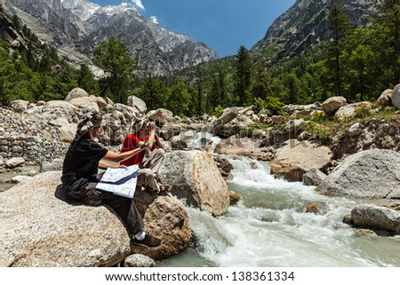 Hiker trekkers discussing route on trek in Himalayas mountains. Himachal Pradesh,India - stock photo