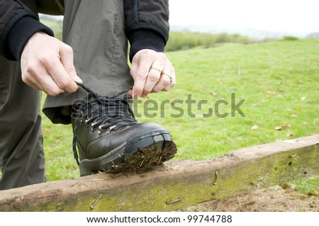 hiker tying boot laces in countryside