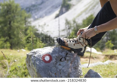 Hiker tying boot laces on rock with signpost, high in the mountains