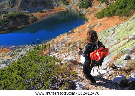 Hiker up on the rocky mountain slope - stock photo