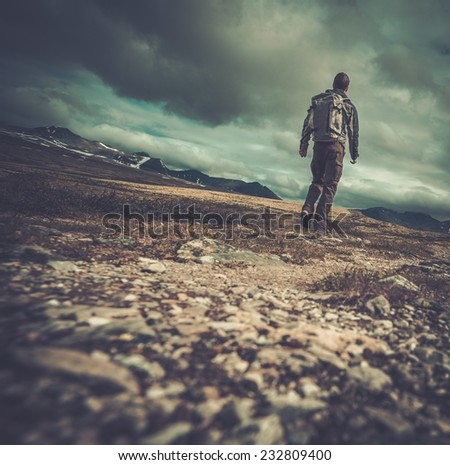 Hiker walking in a valley  - stock photo