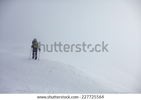 Hiker walking in sunny mountains in wintertime