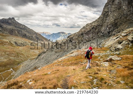 Hiker walking on dangerous footpath crossing a steep rocky slope with great panoramic view and dramatic sky.