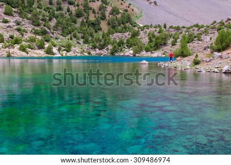 Hiker Walking on Footpath beside Shore Azure Mountain Lake Transparent Water Bottom Stones Well Visible