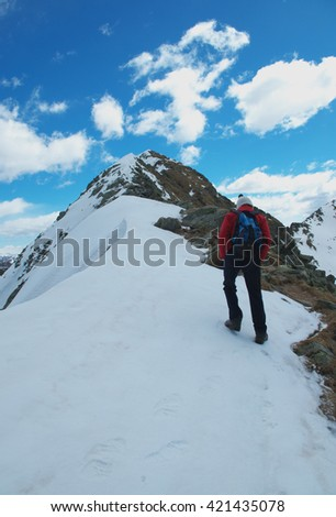 Hiker walking on the snowy ridge of high peak in the Alps Mount Corno Stella, Lombardy, Italy