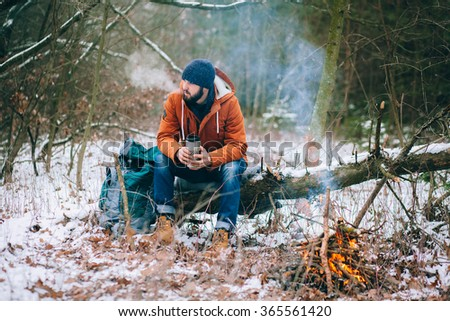 hiker warming hands at campfire in winter forest