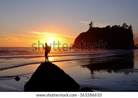 Hiker Watching Sunset at Over the Ocean Surf.  Ruby Beach, Olympic National Park, Washington. - stock photo
