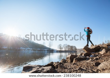Hiker with a backpack hiking in the nature during sunset and drink water - stock photo