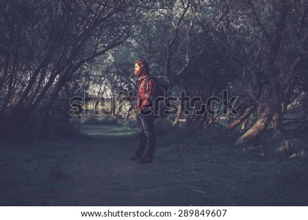 Hiker with a backpack on his back standing in the shade of trees forming an avenue over the trail looking towards the camera with a thoughtful expression