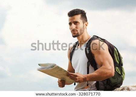 Hiker with a backpack standing on top of the mountain holding a map. Man with map exploring wilderness on trekking adventure. Tourist on the background of the sky