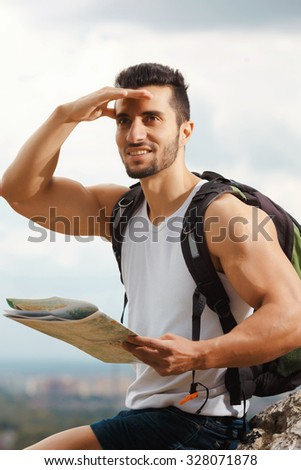 Hiker with a backpack standing on top of the mountain holding a map. Man with map exploring wilderness on trekking adventure. Tourist on the background of the sky - stock photo