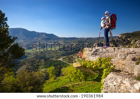 Hiker with baby relaxing on cliff and enjoying valley view. - stock photo