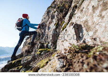 Hiker with backpack and a hat climbing rocky mountain - stock photo