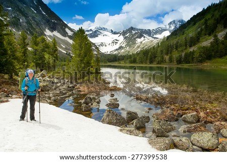 Hiker with backpack and trekking sticks to overcome difficulties in the mountains - stock photo