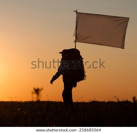 Hiker with backpack and white flag walking in the field. Over sunset. Summer healthy active lifestyle. Single travel. - stock photo