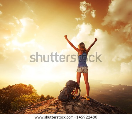 Hiker with backpack enjoying sunrise from top of a mountain - stock photo