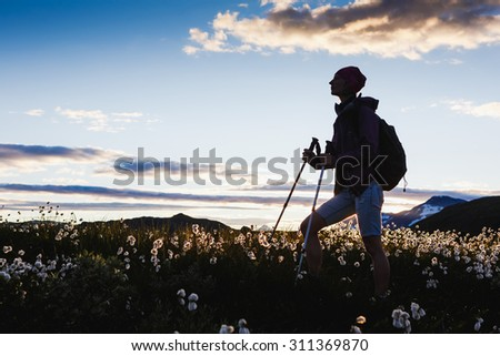 Hiker with backpack enjoying the view with sunset sky background - stock photo