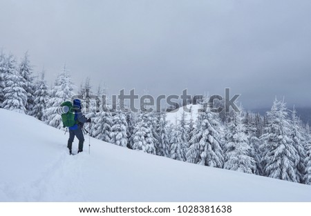 Hiker, with backpack, is climbing on the mountain range, and admires snow-capped peak. Epic adventure in the winter wilderness.