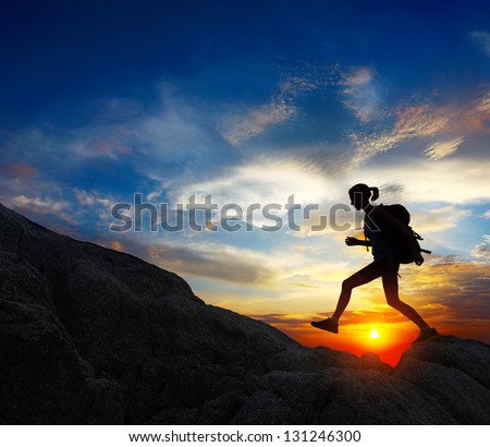 Hiker with backpack jumping over rocks with sunset sky on the background - stock photo