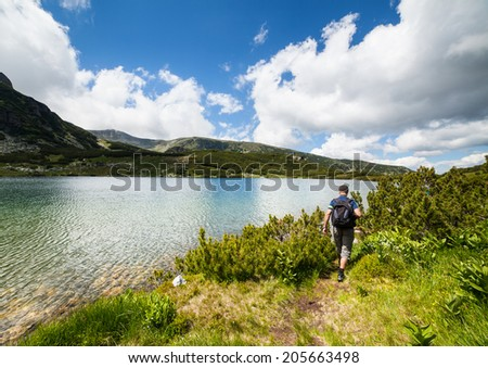 Hiker with backpack nearby a lake in the mountains