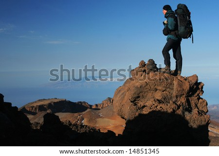 Hiker with backpack on the rock - stock photo