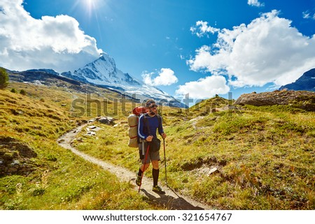 hiker with backpack on the trail in the Apls mountains. Trek near Matterhorn mount