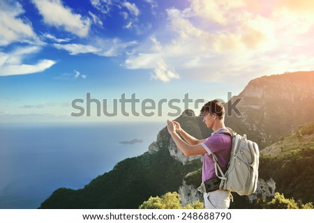 Hiker with backpack on top of the mountain over sea - stock photo