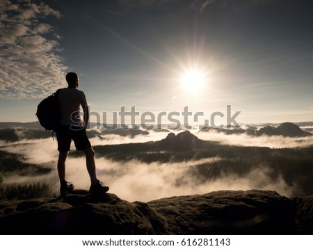 Hiker with backpack reaches the summit of mountain peak. Success, freedom and happiness, achievement in mountains. Active sport concept.