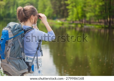 Hiker with backpack relaxing by the lake in a forest and enjoying view of Forest - stock photo