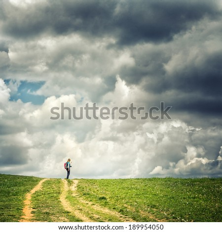 Hiker with backpack relaxing on top and enjoying valley view during cloudy day