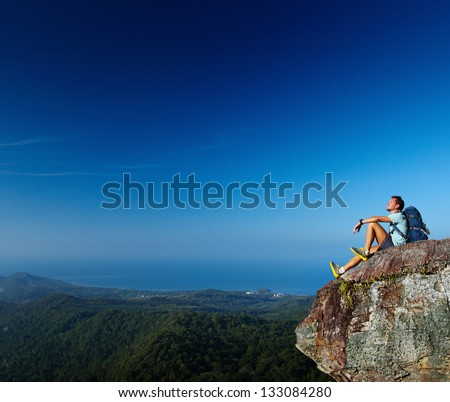 Hiker with backpack relaxing on top of a mountain - stock photo
