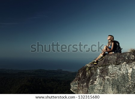 Hiker with backpack relaxing on top of a mountain and enjoying valley view - stock photo