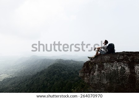 Hiker with backpack relaxing on top of the mountain - stock photo