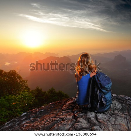 Hiker with backpack sitting on top of a mountain and enjoying sunrise - stock photo