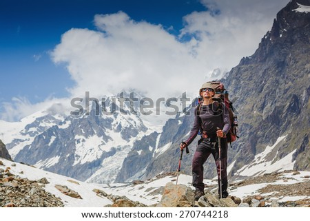 Hiker with backpack standing in the mountains and enjoying the view - stock photo