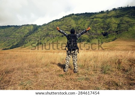 Hiker with backpack standing on a mountain with raised hands and enjoying panorama - stock photo