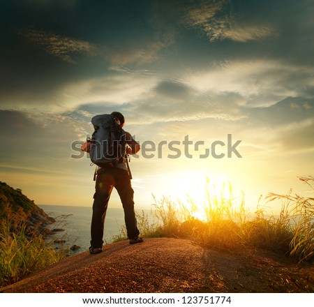 Hiker with backpack standing on a rock and enjoying sunset over sea - stock photo