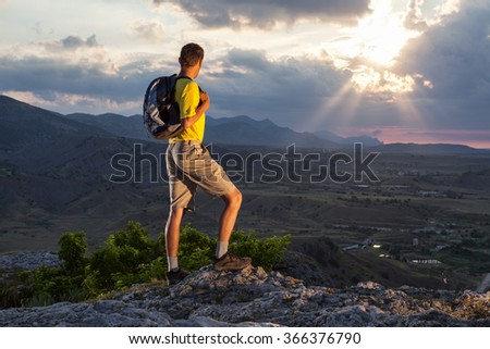 Hiker with backpack standing on a rock and enjoying sunset over valley